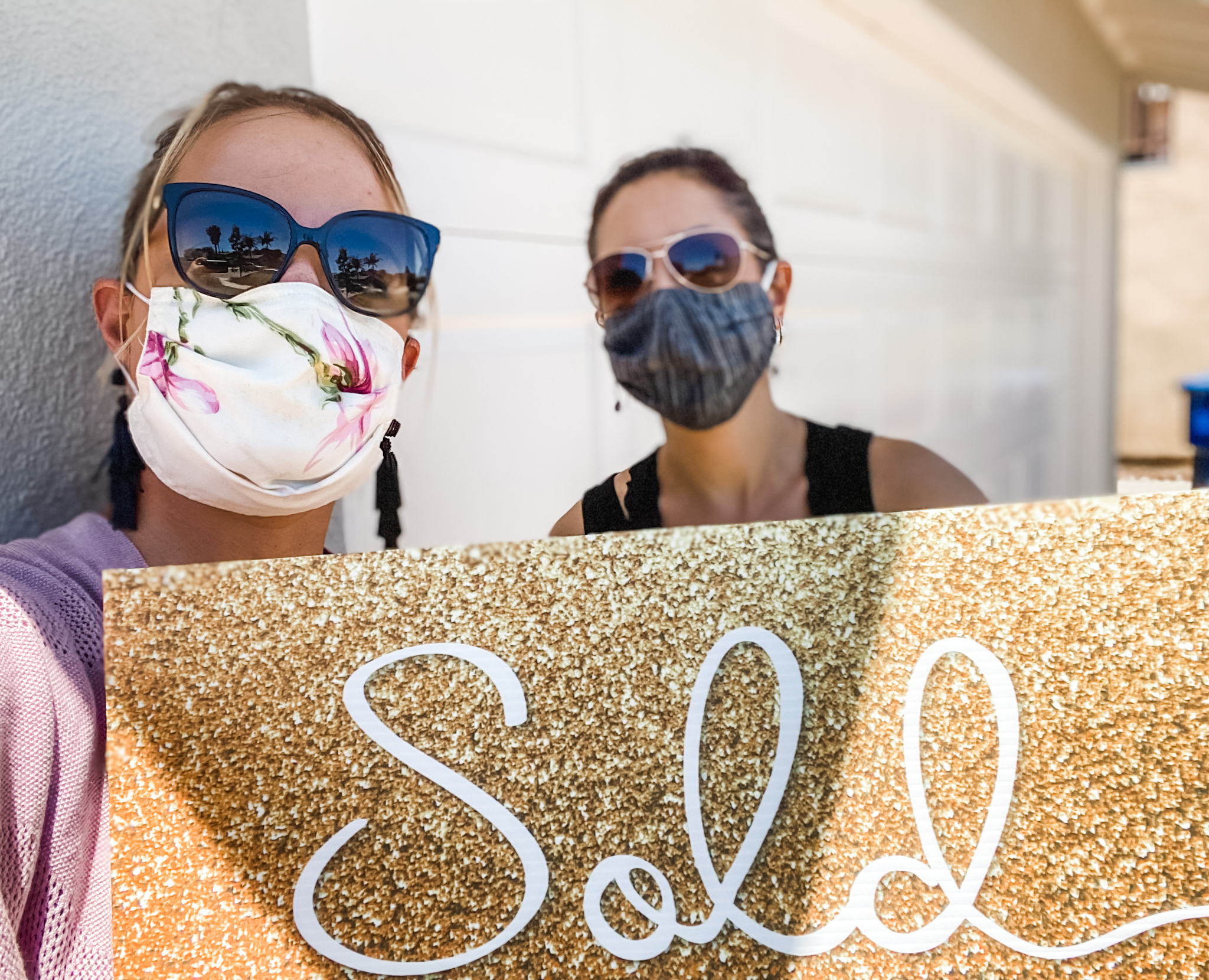 Masked real estate agents with sold sign
